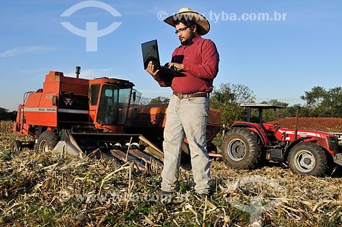 Agricultor com laptop durante a colheita mecanizada de milho  - Mirassol - São Paulo (SP) - Brasil