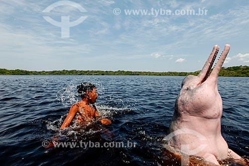 Criança brincando com Boto-cor-de-rosa (Inia geoffrensis) no Rio Negro  - Manaus - Amazonas (AM) - Brasil