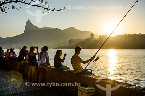 Pessoas observando o pôr do sol e pescando na Mureta da Urca com o Cristo Redentor ao fundo  - Rio de Janeiro - Rio de Janeiro (RJ) - Brasil