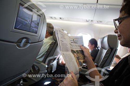 Passageira lendo jornal dentro de avião  - Rio de Janeiro - Rio de Janeiro (RJ) - Brasil