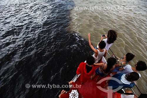 Pessoas observando o encontro das águas do Rio Negro e Rio Solimões a partir da proa do barco  - Manaus - Amazonas (AM) - Brasil