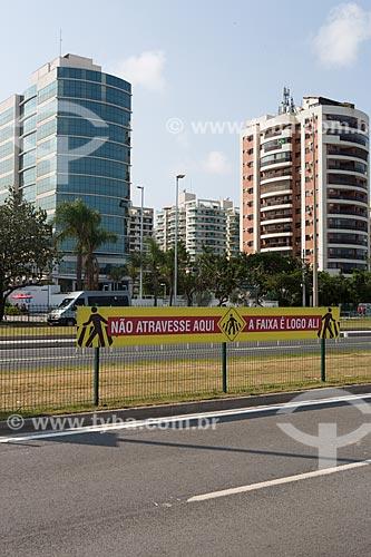 Faixa de aviso com os dizeres: não atravesse aqui a faixa de pedestre é logo ali - para Campanha de Conscientização no Transito na Avenida Embaixador Abelardo Bueno  - Rio de Janeiro - Rio de Janeiro (RJ) - Brasil