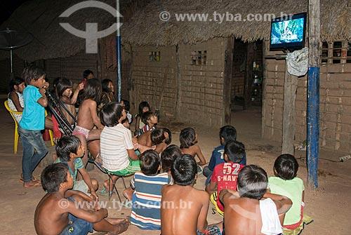 Crianças assistindo televisão no pátio da Aldeia Moikarakô - Terra Indígena Kayapó  - São Félix do Xingu - Pará (PA) - Brasil