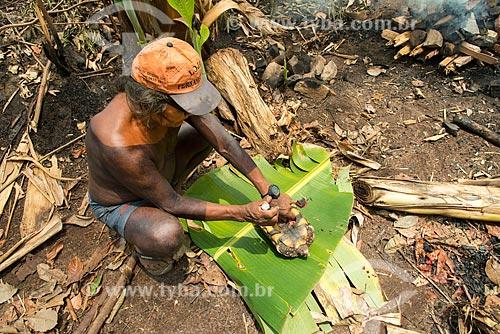 Índio preparando jabuti-piranga (Chelonoidis carbonaria) para assar na Aldeia Moikarakô - Terra Indígena Kayapó  - São Félix do Xingu - Pará (PA) - Brasil