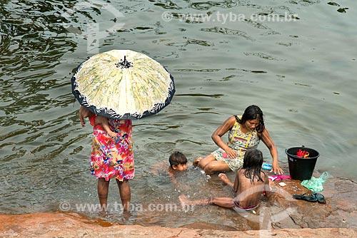 Índia lavando roupas no Rio Riozinho com crianças tomando banho na Aldeia Moikarakô - Terra Indígena Kayapó  - São Félix do Xingu - Pará (PA) - Brasil