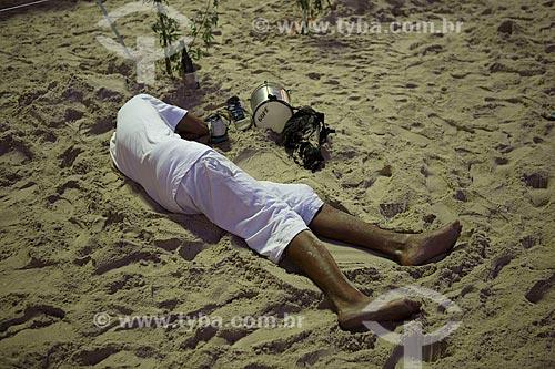 Homem dormindo na areia da Praia de Copacabana - posto 6 - após festa de Réveillon  - Rio de Janeiro - Rio de Janeiro (RJ) - Brasil