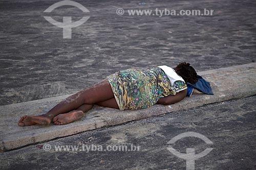 Mulher dormindo na calçada da ciclovia da Praia de Copacabana - posto 6 - após festa de Réveillon  - Rio de Janeiro - Rio de Janeiro (RJ) - Brasil