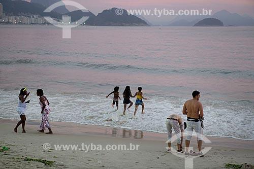 Confraternização de pessoas durante o amanhecer na Praia de Copacabana - posto 6 - após festa de passagem do ano  - Rio de Janeiro - Rio de Janeiro (RJ) - Brasil