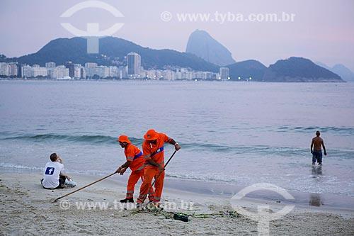 Garis limpando a Praia de Copacabana - posto 6 - após festa de Réveillon - com o Pão de Açúcar ao fundo  - Rio de Janeiro - Rio de Janeiro (RJ) - Brasil