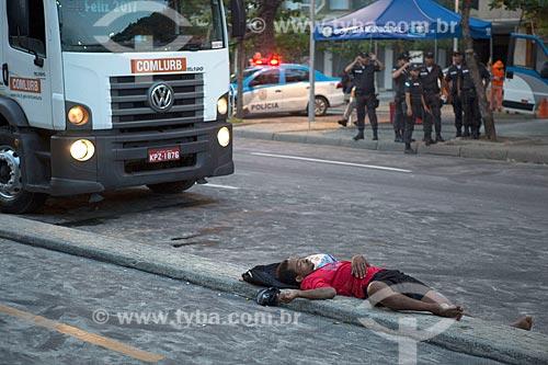 Homem dormindo na calçada da ciclovia da Praia de Copacabana - posto 6 - após festa de Réveillon  - Rio de Janeiro - Rio de Janeiro (RJ) - Brasil