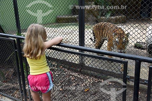 Menina próximo à jaula do tigre (Panthera tigris) no Jardim Zoológico do Rio de Janeiro  - Rio de Janeiro - Rio de Janeiro (RJ) - Brasil