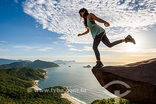 Mulher na Pedra do Telégrafo no Morro de Guaratiba durante o amanhecer  - Rio de Janeiro - Rio de Janeiro (RJ) - Brasil