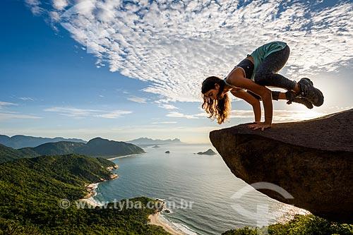 Mulher praticando Yoga - movimento Bakasana (corvo) - na Pedra do Telégrafo no Morro de Guaratiba  - Rio de Janeiro - Rio de Janeiro (RJ) - Brasil