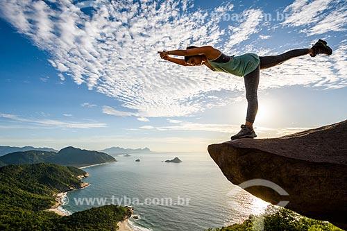 Mulher praticando Yoga - movimento virabhadrasana (guerreiro) - na Pedra do Telégrafo no Morro de Guaratiba  - Rio de Janeiro - Rio de Janeiro (RJ) - Brasil