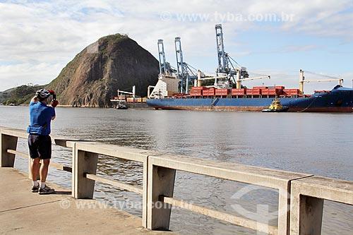 Homem fotografando o navio cargueiro Cândido Rondon no Porto de Vitória com o Monumento Natural Municipal Morro do Penedo ao fundo  - Vila Velha - Espírito Santo (ES) - Brasil