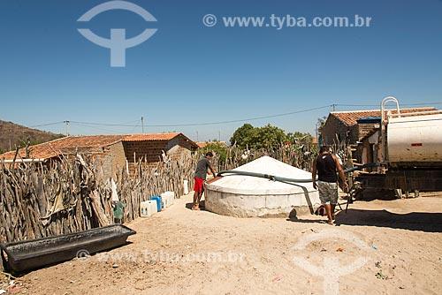Caminhão pipa abastecendo cisterna em casa na Aldeia Capoeira do Barro - Tribo Pipipãs  - Floresta - Pernambuco (PE) - Brasil