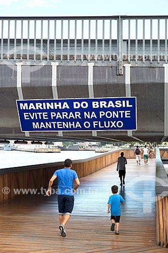 Pessoas caminhando na Orla Prefeito Luiz Paulo Conde com placa com os dizeres: Marinha do Brasil: evite parar na ponte mantenha o fluxo  - Rio de Janeiro - Rio de Janeiro (RJ) - Brasil