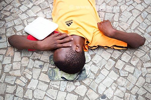 Detalhe de folião deitado em calçada de pedra portuguesa durante o desfile do bloco de carnaval de rua Cordão do Bola Preta  - Rio de Janeiro - Rio de Janeiro (RJ) - Brasil