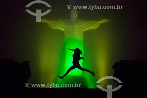 Silhueta de mulher saltando em frente ao Cristo Redentor (1931) com iluminação especial - Verde e Amarelo  - Rio de Janeiro - Rio de Janeiro (RJ) - Brasil
