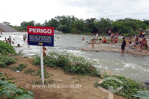Pessoas tomando banho no Rio Paraíba - Projeto de Integração do Rio São Francisco - com placa de aviso que diz: Perigo não se aproxime, mantenha distância, risco de afogamento  - Monteiro - Paraíba (PB) - Brasil