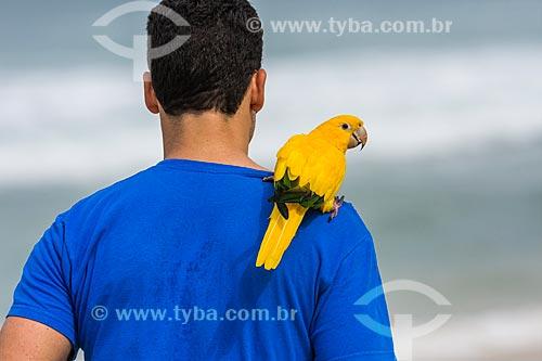 Homem correndo com uma guaruba (Guaruba guarouba) nos ombros na orla da Praia da Barra da Tijuca  - Rio de Janeiro - Rio de Janeiro (RJ) - Brasil