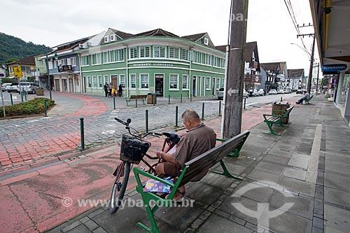 Homem lendo jornal na Rua Luiz Abry com o Restaurante Schroeder ao fundo  - Pomerode - Santa Catarina (SC) - Brasil
