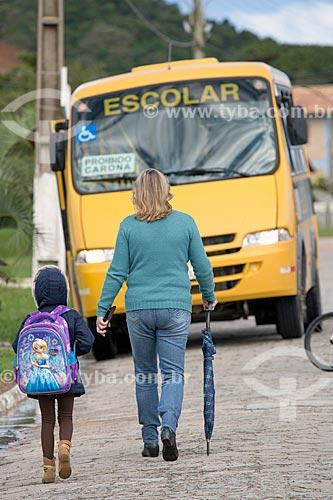 Mulher levando criança para o ônibus escolar  - Laguna - Santa Catarina (SC) - Brasil