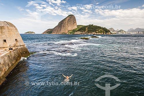 Homem nadando na Baía de Guanabara próximo ao Forte Tamandaré da Laje (1555) com o Pão de Açúcar ao fundo  - Rio de Janeiro - Rio de Janeiro (RJ) - Brasil
