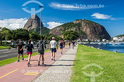 Pessoas caminhando na ciclovia da Praia de Botafogo com o Pão de Açúcar ao fundo  - Rio de Janeiro - Rio de Janeiro (RJ) - Brasil
