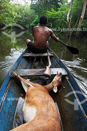 Ribeirinho levando em sua canoa veado caçado na floresta amazônica  - Amazonas (AM) - Brasil