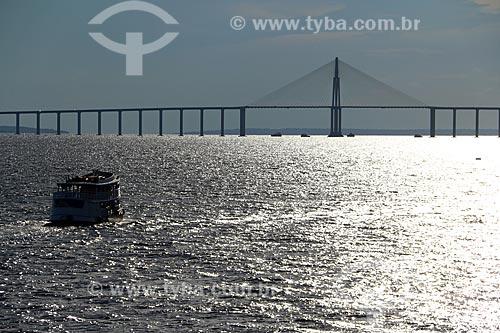 Silhueta de chalana - embarcação regional - no Rio Negro com a Ponte Rio Negro ao fundo durante o pôr do sol  - Manaus - Amazonas (AM) - Brasil