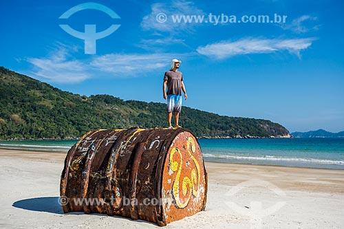 Homem sobre antigo barril de metal encalhado na Praia de Lopes Mendes  - Angra dos Reis - Rio de Janeiro (RJ) - Brasil