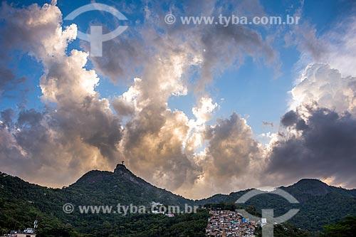 Vista do Cristo Redentor a partir do bairro de Cosme Velho durante o pôr do sol com a Favela do Cerro Corá à direita  - Rio de Janeiro - Rio de Janeiro (RJ) - Brasil