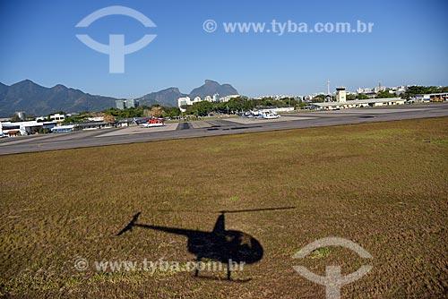 Sombra de helicóptero no Aeroporto Roberto Marinho - mais conhecido como Aeroporto de Jacarepaguá - com a Pedra da Gávea ao fundo  - Rio de Janeiro - Rio de Janeiro (RJ) - Brasil