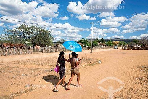 Índias na aldeia Travessão do Ouro da Tribo Pipipãs protegendo bebê do sol com sombrinha  - Floresta - Pernambuco (PE) - Brasil