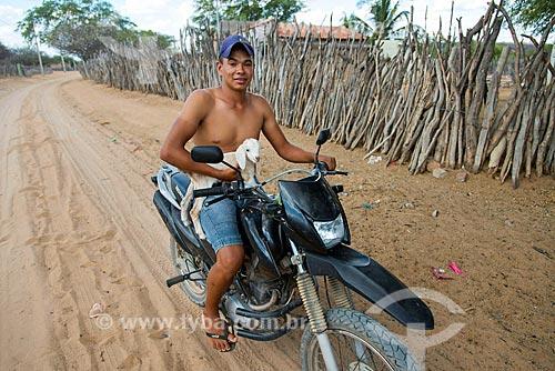 Índio da aldeia Travessão do Ouro da Tribo Pipipãs carregando bezerro em moto  - Floresta - Pernambuco (PE) - Brasil