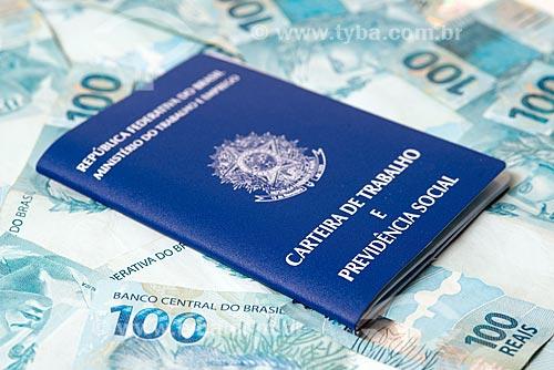 Detalhe de carteira de trabalho sobre notas de 100 reais  - Rio de Janeiro - Rio de Janeiro (RJ) - Brasil