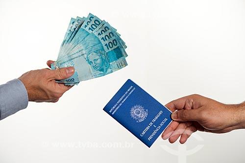 Detalhe de mão segurando notas de 100 reais - à esquerda - e mão segurando carteira de trabalho - à direita  - Rio de Janeiro - Rio de Janeiro (RJ) - Brasil
