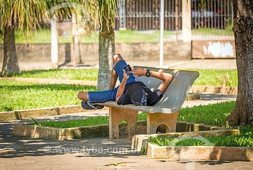 Adolescente usando celular deitado em banco de praça  - Guarani - Minas Gerais (MG) - Brasil