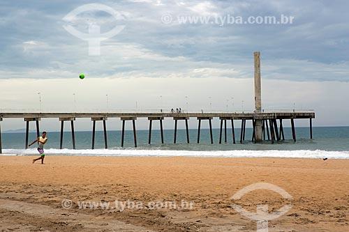 Jovem jogando futebol na orla da Praia de Costazul com o Emissário submarino ao fundo  - Rio das Ostras - Rio de Janeiro (RJ) - Brasil