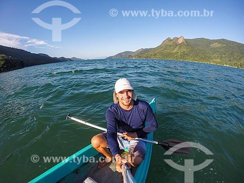 Homem fazendo uma selfie em caiaque na orla da Praia do Cruzeiro com o Pico do Pão de Açúcar - também conhecido como Pico do Mamanguá - ao fundo  - Paraty - Rio de Janeiro (RJ) - Brasil