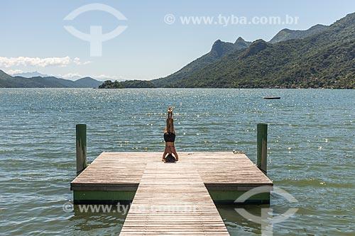 Mulher praticando Yoga - movimento sirsasana - em cais na Praia da Ponta do Bananal  - Paraty - Rio de Janeiro (RJ) - Brasil