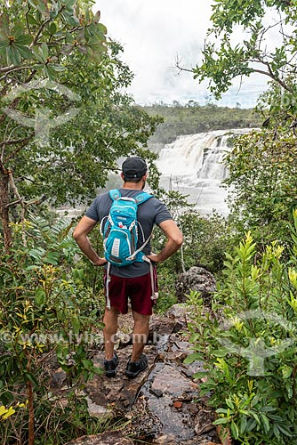 Homem em trilha do Parque Nacional da Chapada dos Veadeiros com o Cachoeira dos Couros ao fundo  - Alto Paraíso de Goiás - Goiás (GO) - Brasil