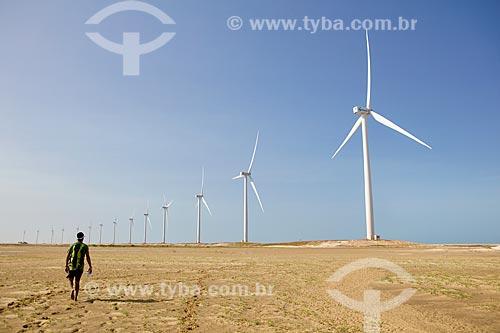 Homem andando nas dunas do Delta do Parnaíba com o do Parque Eólico Pedra do Sal ao fundo  - Ilha Grande - Piauí (PI) - Brasil