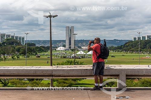 Homem fotografando o centro de Brasília com o Congresso Nacional ao fundo  - Brasília - Distrito Federal (DF) - Brasil