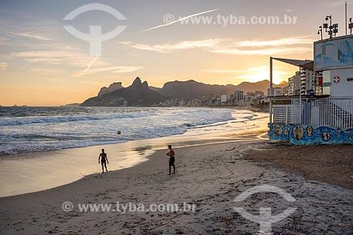 Banhistas jogando futebol (altinha) na orla da Praia de Ipanema durante o pôr do sol com a Pedra da Gávea e o Morro Dois Irmãos ao fundo  - Rio de Janeiro - Rio de Janeiro (RJ) - Brasil