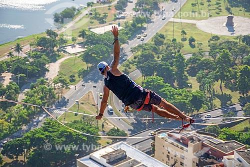 Detalhe de homem praticando o movimento Plano inclinado lateral (Vashistasana) em slackline no Morro do Cantagalo  - Rio de Janeiro - Rio de Janeiro (RJ) - Brasil