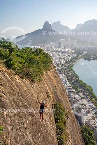 Praticante de slackline no Morro do Cantagalo com o Morro Dois Irmãos e a Pedra da Gávea ao fundo  - Rio de Janeiro - Rio de Janeiro (RJ) - Brasil