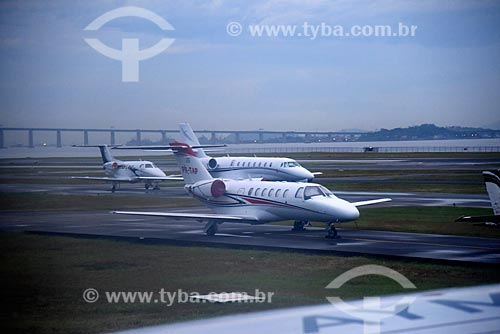 Aviões na pista do Aeroporto Santos Dumont com a Ponte Rio-Niterói ao fundo  - Rio de Janeiro - Rio de Janeiro (RJ) - Brasil