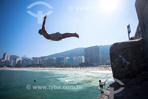 Jovem saltando no mar a partir do Mirante do Leme - também conhecido como Caminho dos Pescadores  - Rio de Janeiro - Rio de Janeiro (RJ) - Brasil